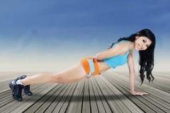 Das attraktive Frauenhandeln drückt Übung hoch Lizenzfreies Stockfoto