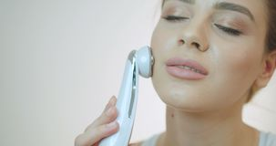 Das attraktive frische schöne Mädchen mit Porzellanhaut und natürlichem Make-up benutzt den elektrischen Gesicht Massager über stock video