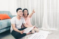 Das attraktive junge asiatische erwachsene Paar, das Haus betrachtet, plant stockfotografie