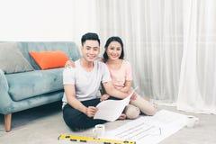 Das attraktive junge asiatische erwachsene Paar, das Haus betrachtet, plant lizenzfreies stockfoto
