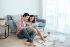 Das attraktive junge asiatische erwachsene Paar, das Haus betrachtet, plant lizenzfreies stockbild