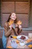 Das attraktive junge Mädchen, das in einem Café sitzt, lächelnd mit ihren Augen, schloss und hielt ein gefallenes Laub lizenzfreie stockbilder