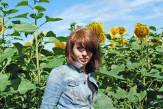 Das attraktive Mädchen auf dem Gebiet von Sonnenblumen Stockbilder