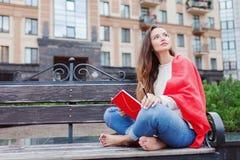 Das attraktive Mädchen, das auf einer Bank mit den bloßen Füßen, umfasst mit einer roten Decke, im neuen Wohngebiet sitzt und sch lizenzfreies stockfoto