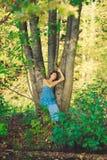 Das attraktive Mädchen, das auf der Bank des Sees sitzt Stockfotografie