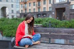 Das attraktive Mädchen, das auf einer Bank mit den bloßen Füßen, umfasst mit einer roten Decke, im neuen Wohngebiet sitzt und sch Stockfoto