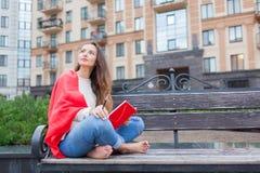 Das attraktive Mädchen, das auf einer Bank mit den bloßen Füßen, umfasst mit einer roten Decke, im neuen Wohngebiet sitzt und sch Stockbilder