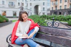 Das attraktive Mädchen, das auf einer Bank mit den bloßen Füßen, umfasst mit einer roten Decke, im neuen Wohngebiet sitzt und sch Stockfotos