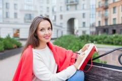 Das attraktive Mädchen, das auf einer Bank mit den bloßen Füßen, umfasst mit einer roten Decke, im neuen Wohngebiet sitzt und sch Lizenzfreie Stockfotos
