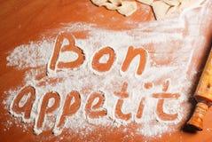 Das Aufschrift Bon appetit auf dem Tisch mit Mehl lizenzfreie stockbilder