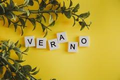 Das Aufschrift verano auf spanisch auf den Buchstaben der Tastatur auf einem gelben Hintergrund mit Niederlassungen von Blumen lizenzfreie stockbilder