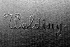 Das Aufschriftschweißen, tig-Schweißensgriff auf einer Metallplatte Stockbilder