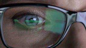 Das Auge der Nahaufnahmefrau in den Gläsern arbeitet an Laptop nachts stock video