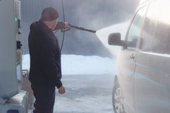 Das Auto auf einer kontaktlosen Wanne waschend, wäscht ein Mann seinen weißen Packwagen stockfotos