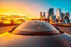 Das Auto bewegt sich an der hohen Geschwindigkeit zur Sonnenuntergangzeit lizenzfreies stockfoto