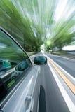 Das Auto bewegt sich mit großer Drehzahl am sonnigen Tag. Lizenzfreie Stockbilder
