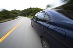 Das Auto bewegt sich mit großer Geschwindigkeit an der Gebirgsstraße stockbilder