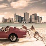 Das Auto, das jugendlich Mädchen drückt, geben das lustige Kerlfahren nach Stockfoto