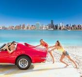 Das Auto, das jugendlich Mädchen drückt, geben das lustige Kerlfahren nach Stockfotos