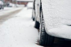 Das Auto, das mit Schnee bedeckt wurde, parkte auf der Straße Stockfotografie