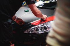 Das Auto, das Spezialisten einwickelt, arbeitet an einer Autoshow Stockfoto