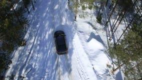 Das Auto fährt auf eine Winterstraße unter dem Holz und