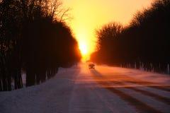 Das Auto geht bei Sonnenuntergang auf einer schneebedeckten Straße des Winters in einem Schneesturm Stockbilder