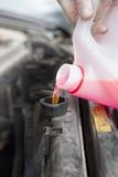Das Auto hob auf den Aufzug und eine Schüssel für Schmierölwiedereinbau an Hinzufügen der Flüssigkeit dem Auto ` s Heizkörper lizenzfreie stockfotografie
