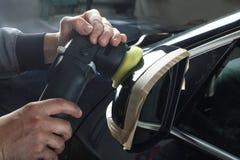 Das Auto hob auf den Aufzug und eine Schüssel für Schmierölwiedereinbau an Polierspiegel des Autos Lizenzfreie Stockfotos