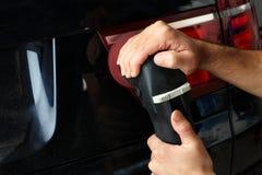 Das Auto hob auf den Aufzug und eine Schüssel für Schmierölwiedereinbau an Polnisch der hinteren Optik des Autos Lizenzfreie Stockfotos