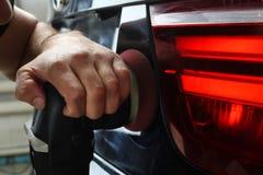 Das Auto hob auf den Aufzug und eine Schüssel für Schmierölwiedereinbau an Polnisch der hinteren Optik des Autos Lizenzfreies Stockfoto