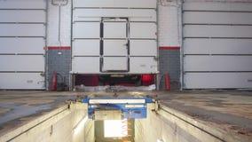 Das Auto hob auf den Aufzug und eine Schüssel für Schmierölwiedereinbau an Starker Mechanikermann, der eine Garage öffnet Das Aut stock footage
