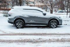 Das Auto im Schnee, bedeckt mit einer weißen Schneewehe Stockfotos