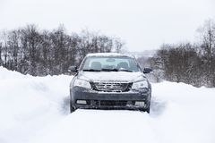 Das Auto steht auf einer schneebedeckten Straße Lizenzfreies Stockbild