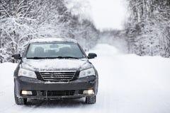 Das Auto steht auf einer schneebedeckten Straße Stockbild