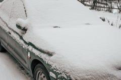 Das Auto wird mit Schnee der Parkplatz, ein schmutziges Auto im Schnee, im Winter im Parkplatz bedeckt Lizenzfreies Stockbild