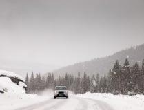 Das Autofahren entlang Schnee bedeckte Straße in einem Schneesturm Lizenzfreie Stockbilder