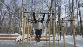 Das bärtige Mannhandeln zieht Übung während Trainings des im Freien auf Sportplatz hoch stockfotografie