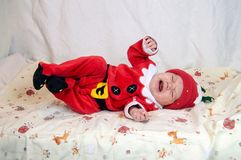 Das Baby, das als Santa Claus gekleidet wird, ist im Bett frech stockfoto