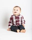 Das Baby, das im Flanell und in Jeans oben schauen sitzt und verließ lizenzfreie stockfotos