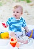 Das Baby, das mit Strand spielt, spielt auf dem Strand Stockbilder