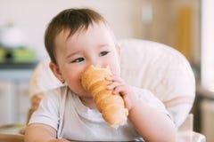 Das Baby in der K?che isst gierig die k?stlichen sahnigen Rohre, die mit Vanillecreme gef?llt werden stockbild