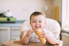 Das Baby in der K?che isst gierig die k?stlichen sahnigen Rohre, die mit Vanillecreme gef?llt werden lizenzfreie stockfotos