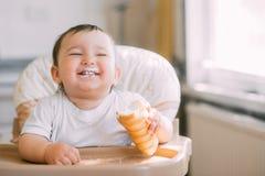Das Baby in der K?che isst gierig die k?stlichen sahnigen Rohre, die mit Vanillecreme gef?llt werden stockbilder