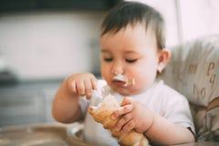 Das Baby in der K?che isst gierig die k?stlichen sahnigen Rohre, die mit Vanillecreme gef?llt werden stockfotos