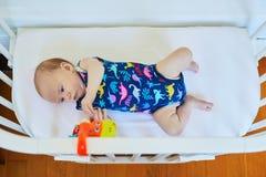 Das Baby, das in der Mitlagerschwelle liegt, befestigte zu Eltern ` Bett Lizenzfreie Stockfotografie