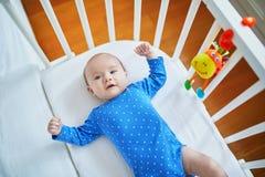 Das Baby, das in der Mitlagerschwelle liegt, befestigte zu Eltern ` Bett Stockbild