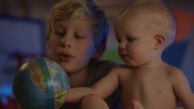 Das Baby, das gerade an schlechtem sitzt und mit Kugel und seinem Bruder spielt, macht Firmenflusskamera stock video