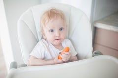 Das Baby isst Karotten stockfoto