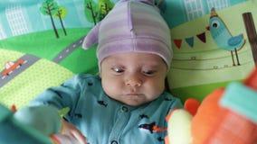 Das Baby liegt auf der sich entwickelnden Wolldecke stock video